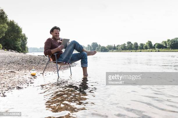 mature man using tablet at rhine riverbank - sober leven stockfoto's en -beelden