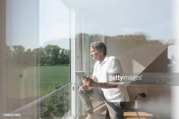 mature man using tablet at the window - investition stock-fotos und bilder