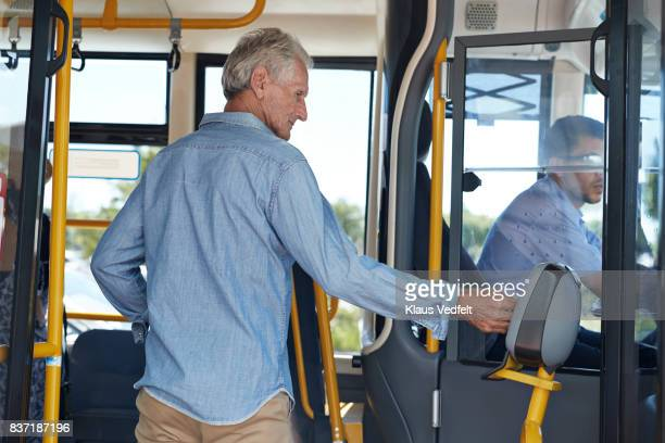 Mature man using travel card to pay for bus ride