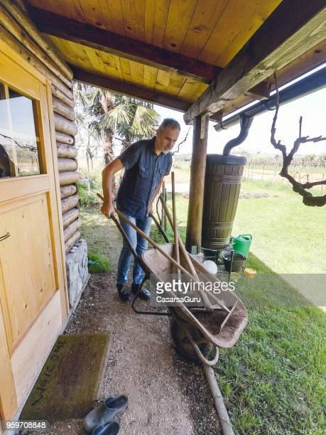成熟した彼の小屋の周りの手押し車を使用している人 - 掘建て小屋 ストックフォトと画像