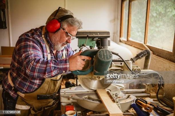 mature man using workshop machinery - tradition stock pictures, royalty-free photos & images