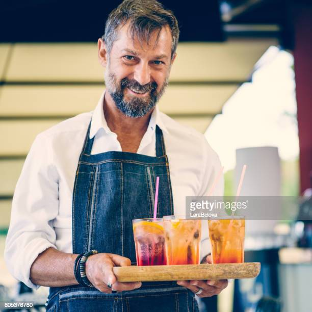 mature man waiter in sidewalk cafe - missing people stock photos and pictures