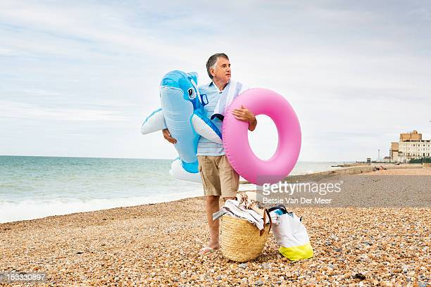 Mature man waiting with beach accessoires.