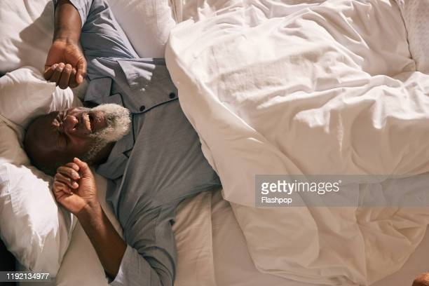 mature man wakes in bed - yawning stock pictures, royalty-free photos & images