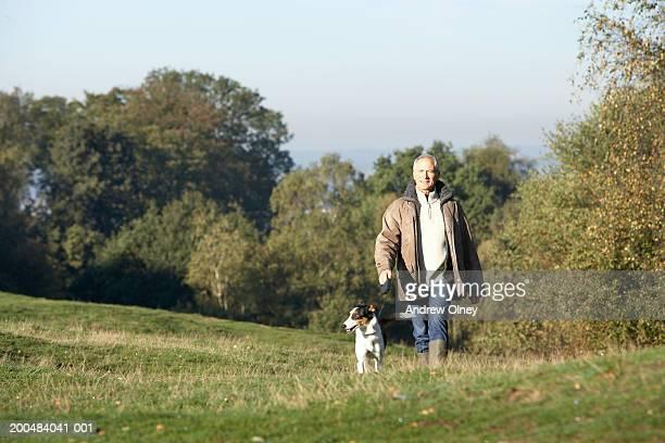 Mature man walking dog in countryside