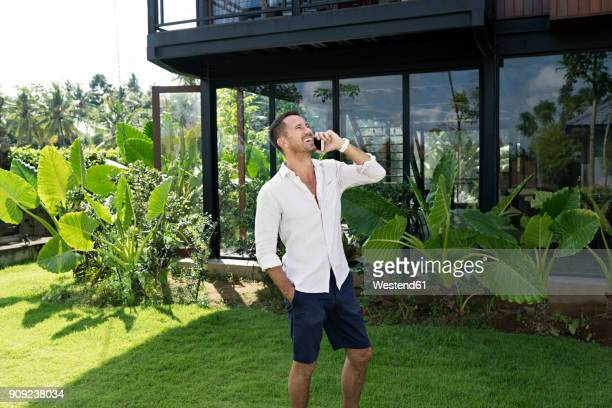 Mature man walking in garden in front of modern villa, using smartphone