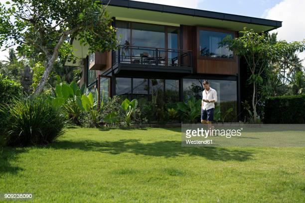 mature man walking in garden in front of modern villa, using smartphone - premium access stock pictures, royalty-free photos & images