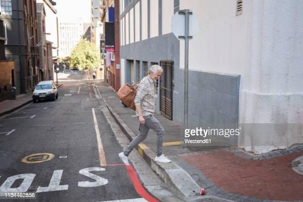 mature man walking in the city, carrying bag - cruzar fotografías e imágenes de stock