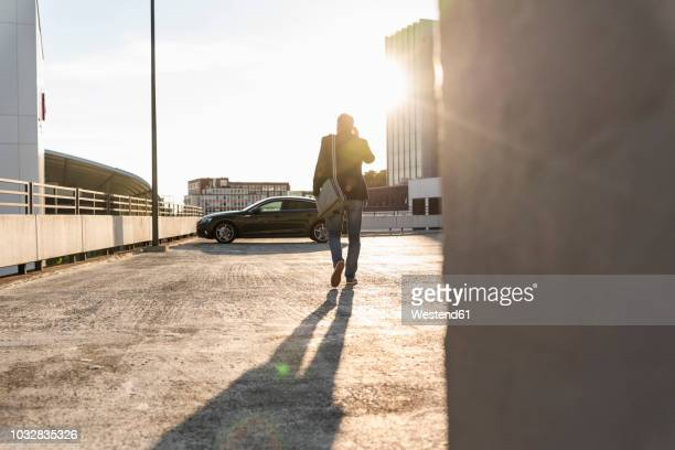 mature man walking on parking level to his car, talking at the phone - gegenlicht stock-fotos und bilder