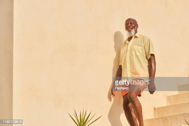 mature man walks down stairs - disruptaging stock pictures, royalty-free photos & images