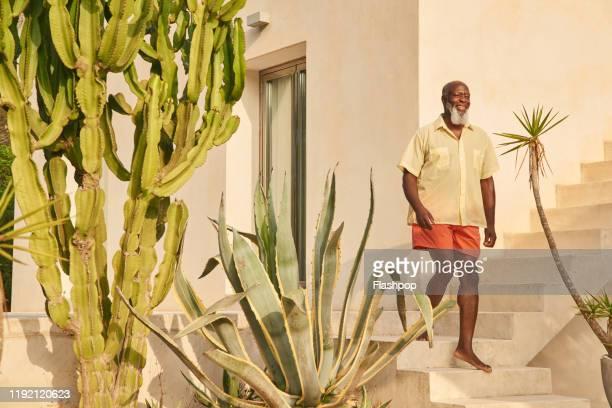 mature man walks down stairs - pieds nus photos et images de collection