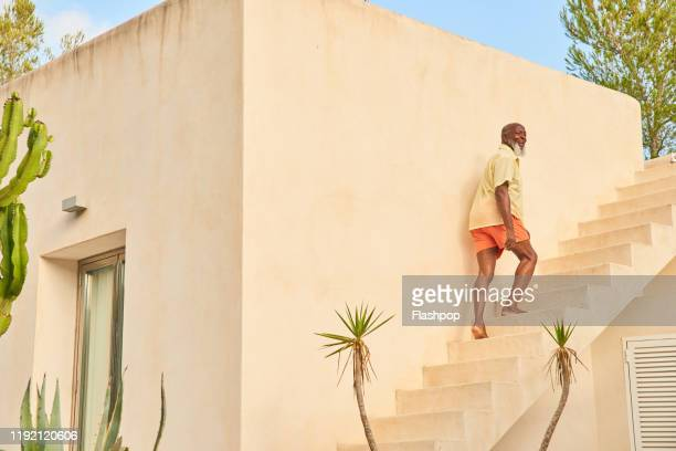 mature man walks up stairs - europa meridionale foto e immagini stock