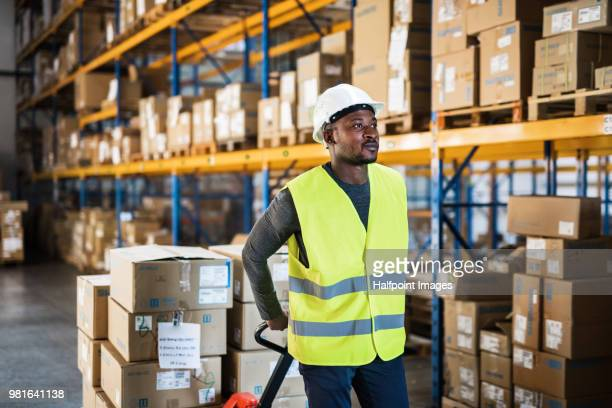 mature man warehouse worker with reflexive waistcoat pulling a pallet truck with boxes. - waistcoat stock photos and pictures