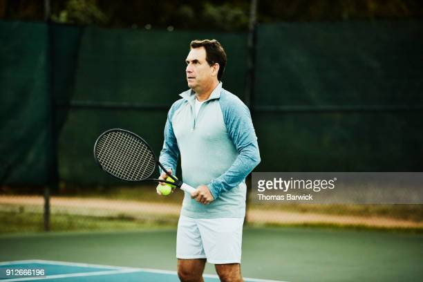 Mature man warming up for early morning tennis match