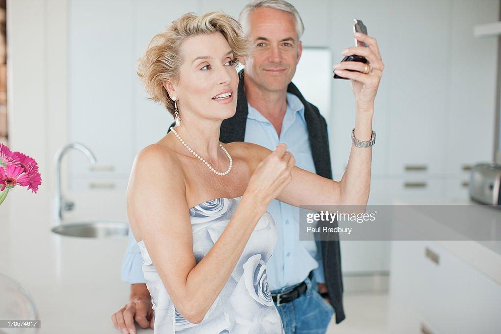 Mature man watching woman apply makeup : Stock Photo