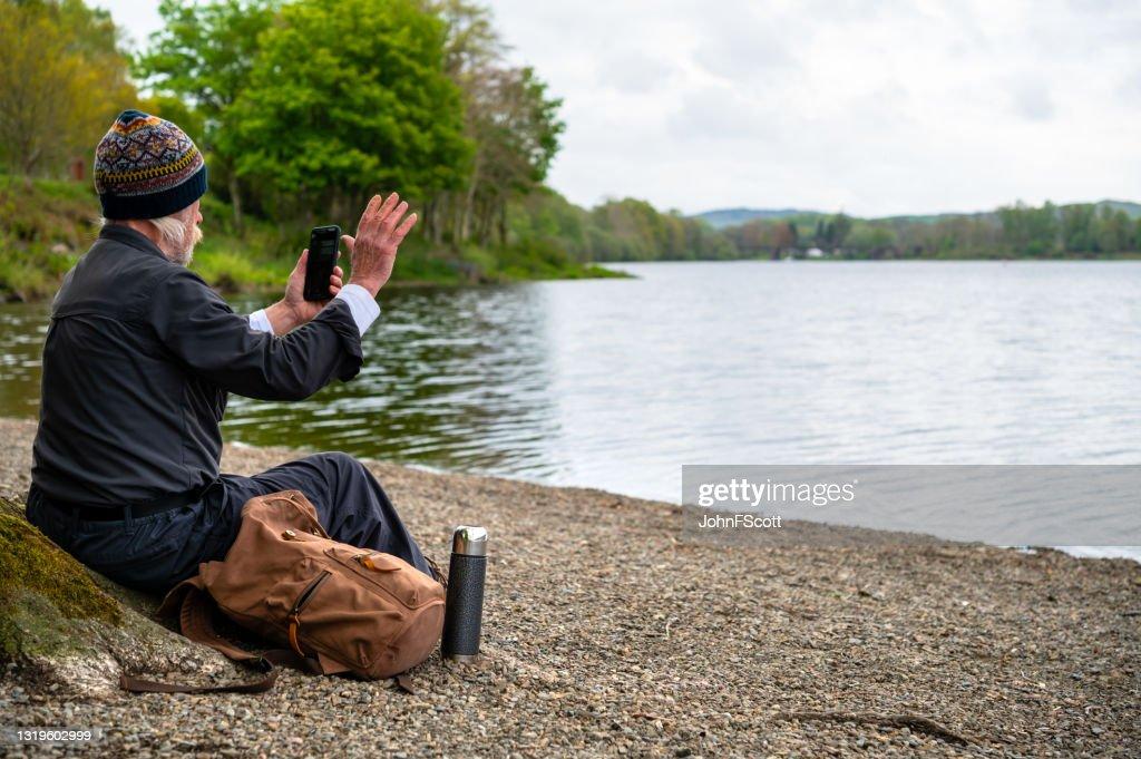 Mature man waving at a mobile phone : Stock Photo