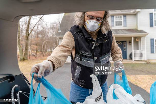 mature man wearing a protective mask and gloves unloading plastic reusable bins filled with groceries from the car's trunk to be delivered. - alex potemkin coronavirus stock pictures, royalty-free photos & images