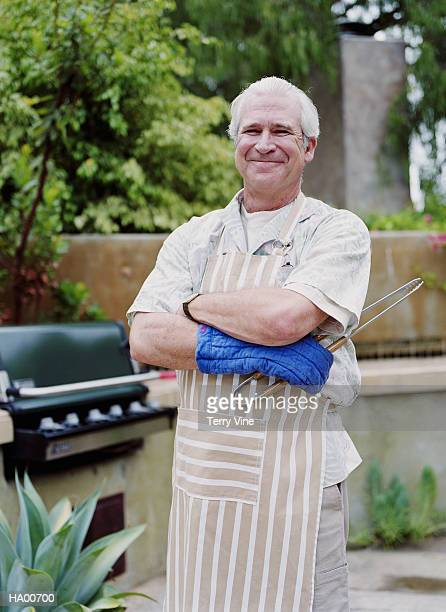 Mature man wearing apron, standing next to barbeque, portrait