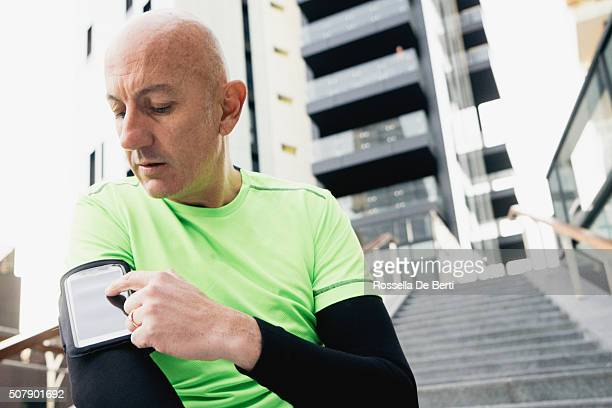 Mature Man Wearing Arm Band Using Smartphone During Workout