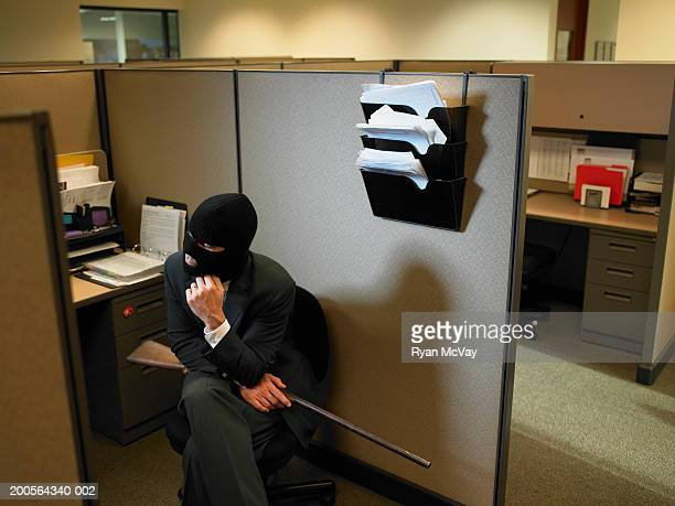 Mature man wearing balaclava, holding rifle, squatting at office