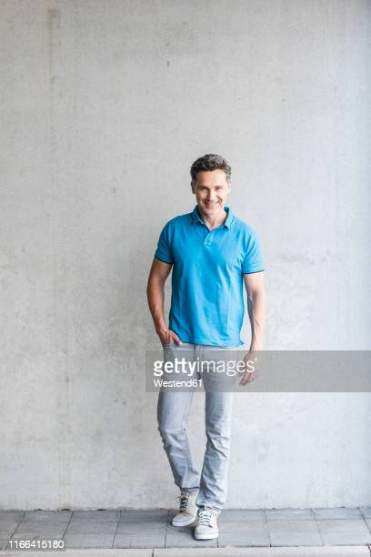 mature man wearing blue poloshirt, grey wall in the background - ポロシャツ ストックフォトと画像