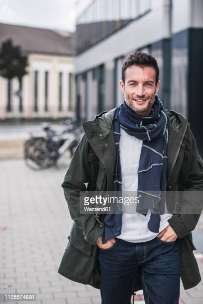 mature man, wearing coat and scarf, walking in the city, with hands in pockets - mantel stock-fotos und bilder