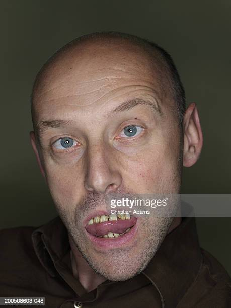 mature man wearing fake teeth, making funny face, close-up, portrait - ugly bald man fotografías e imágenes de stock
