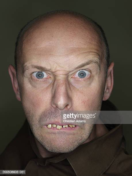 mature man wearing fake teeth, making funny face, close-up, portrait - ugly bald man stock photos and pictures