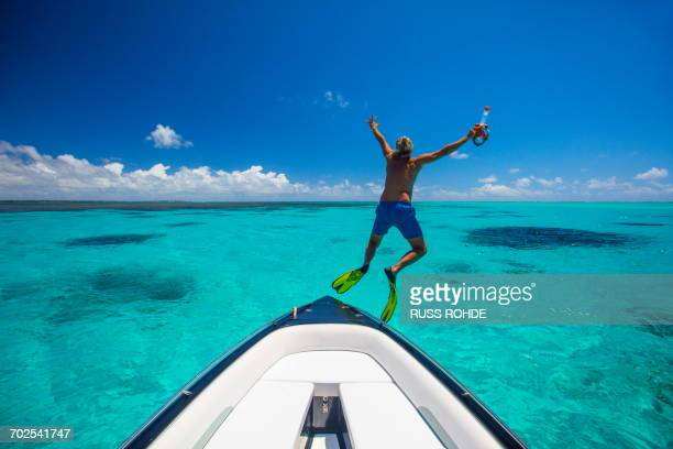 Mature man, wearing flippers, jumping off boat, Ile aux Cerfs, Mauritius