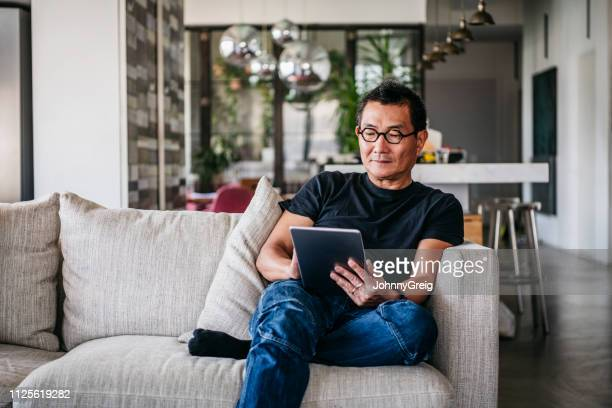 mature man wearing glasses using digital tablet - reading stock pictures, royalty-free photos & images