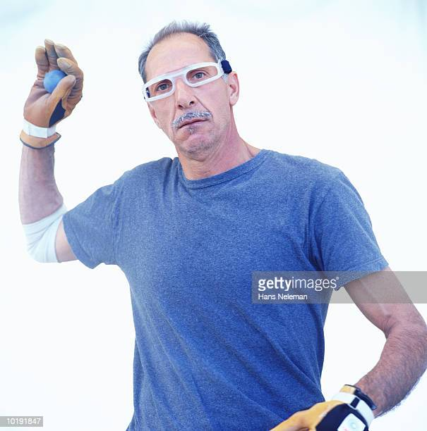 Mature man wearing gloves, holding ball, portrait