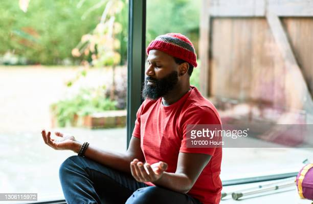 mature man wearing hat meditating in yoga class - tranquility stock pictures, royalty-free photos & images