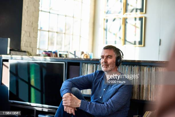 mature man wearing headphones and looking thoughtful - freizeitaktivität stock-fotos und bilder