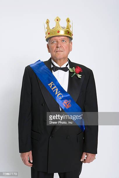 Mature man wearing king's crown and sash, looking up