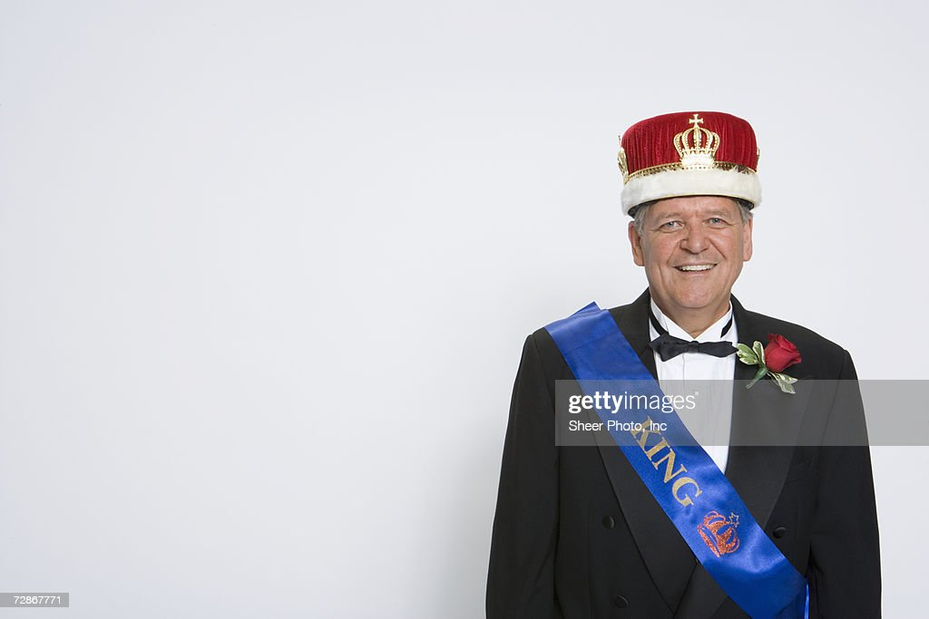 Mature man wearing king's crown and sash, smiling, portrait : Stock Photo