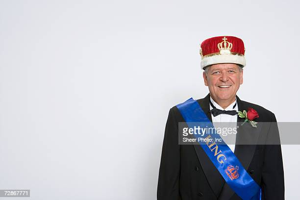 Mature man wearing king's crown and sash, smiling, portrait