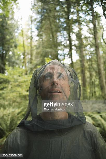 mature man wearing mosquito netting suit in forest, looking up - mosquito net stock photos and pictures