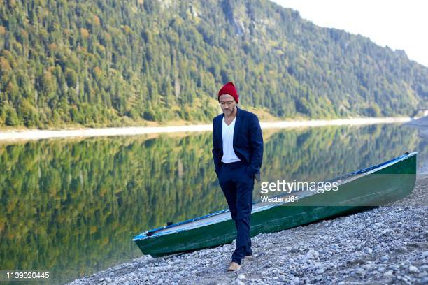 mature man wearing red cap and blue suit walking barefoot at lakeshore - hands in pockets stock pictures, royalty-free photos & images