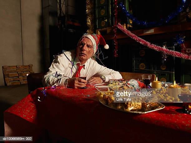 Mature man wearing santa hat, holding wine glass sitting at christmas table in warehouse