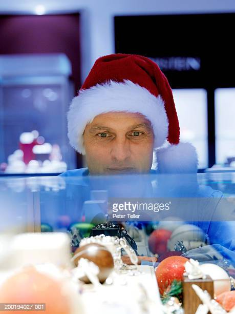 Mature man wearing santa hat looking in shop display cabinet, close-up