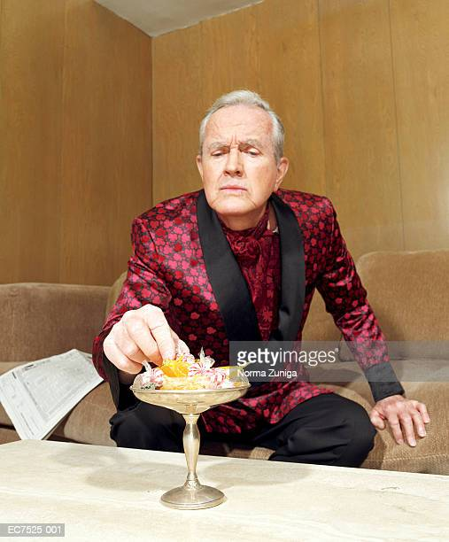 mature man wearing silk robe, picking candy from dish - smoking jacket stock photos and pictures