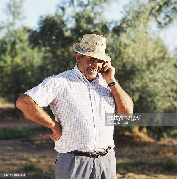 Mature man wearing straw hat using mobile phone outdoors