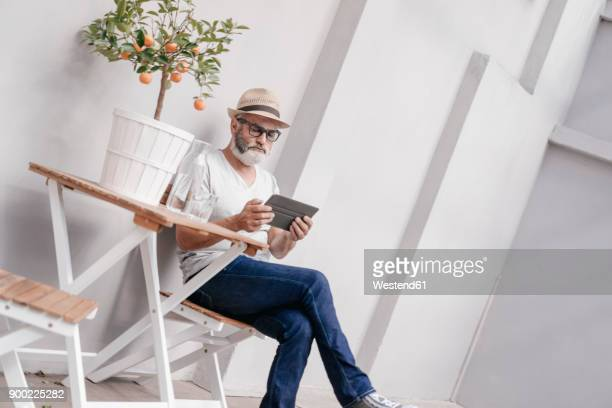 Mature man wearing straw hat using tablet next to table with orange tree