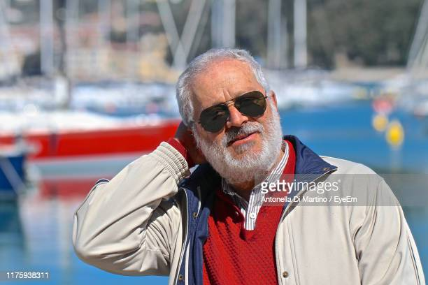 mature man wearing sunglasses at harbor - antonella di martino foto e immagini stock