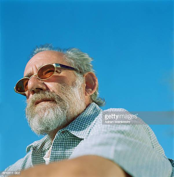 mature man wearing sunglasses, outdoors, close-up - lunettes de soleil teintées photos et images de collection