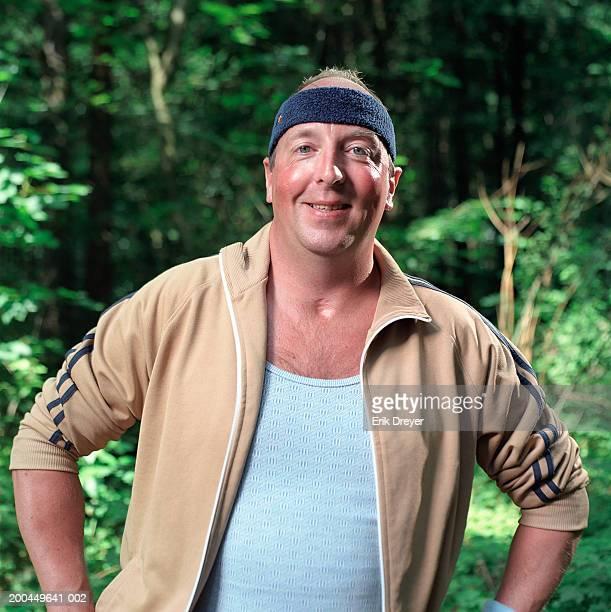mature man wearing sweatband standing in forest, smiling, portrait - trainingsanzug stock-fotos und bilder