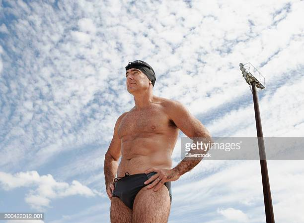 Mature man wearing swimming trunks and cap outdoors