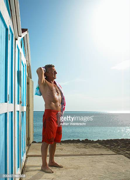 mature man wearing swimming trunks drying hair with towel by beach hut - zwembroek stockfoto's en -beelden