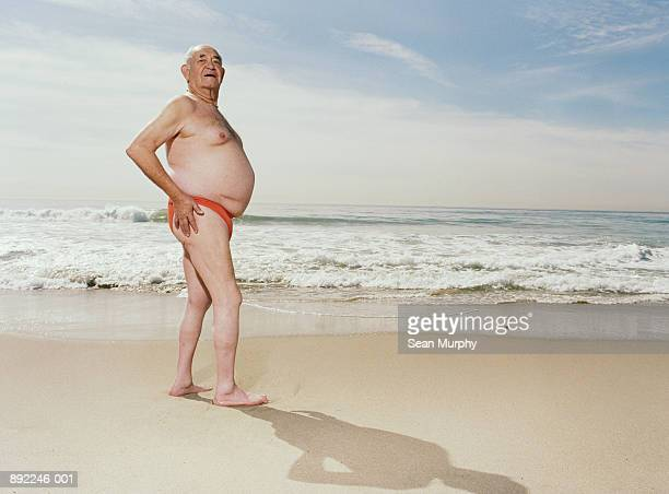 mature man wearing swimsuit on beach - fat man speedo stock pictures, royalty-free photos & images