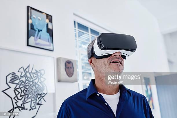 Mature man wearing virtual reality glasses